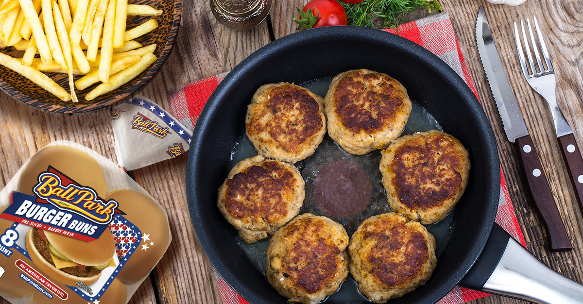 An overhead photo of a pan with six turkey burgers in it.