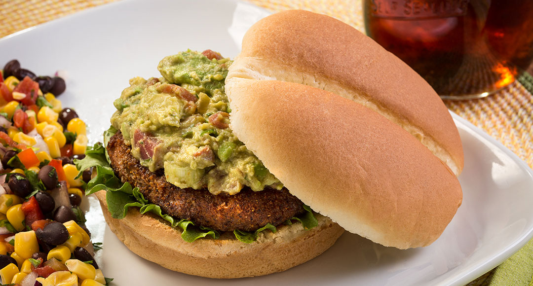 A photo of Ball Park's Guacamole Turkey Burger, served with a corn and bean salad