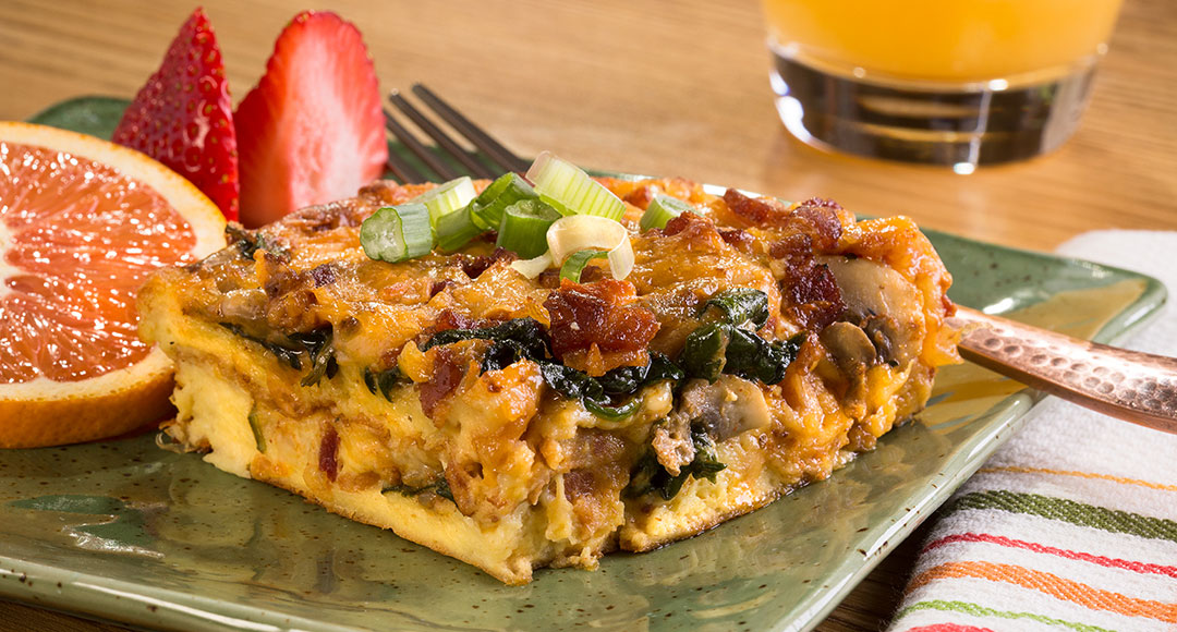 A photo of Ball Park's Spinach-Mushroom Brunch Casserole served with a side of fruit