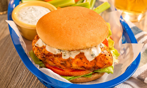 A photo of Ball Park's Spicy Buffalo Chicken Sandwich served with a side of blue cheese dressing and celery sticks
