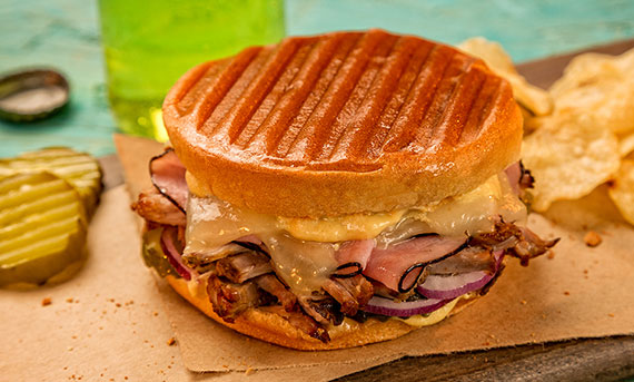 A photo of Ball Park's Grilled Cuban Bunini Sandwich, served with potato chips