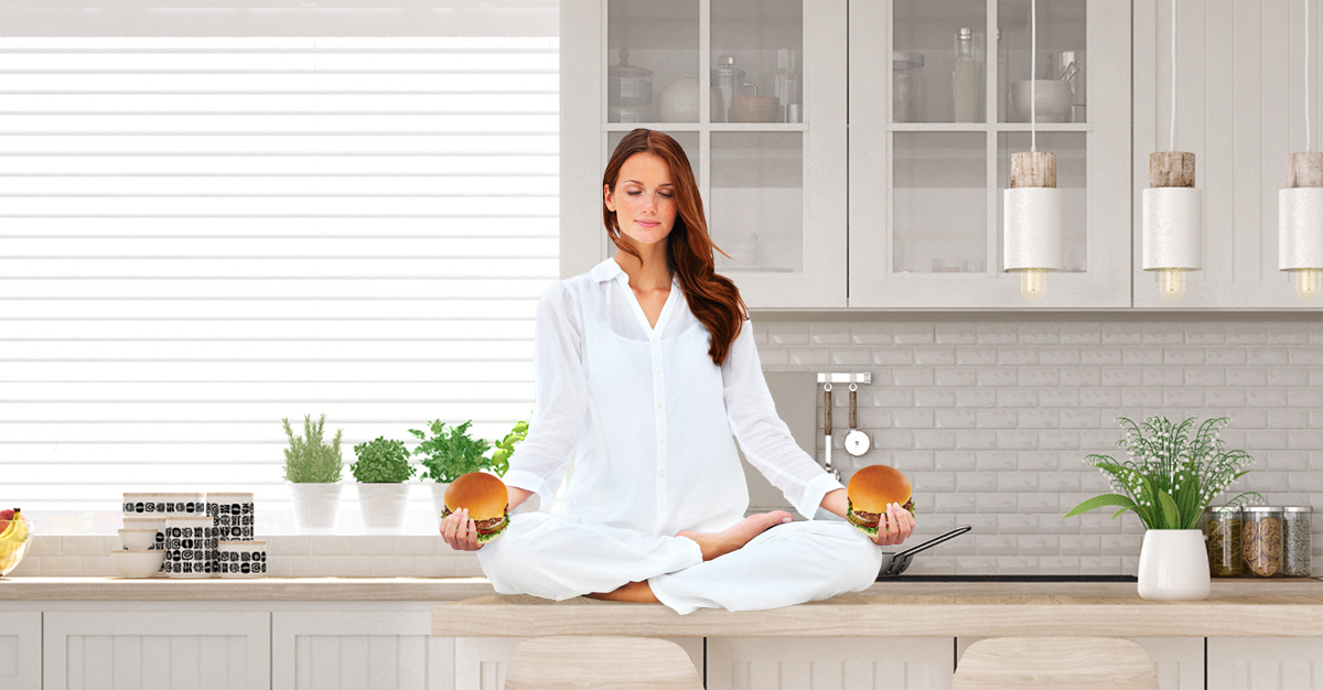 A photo of a woman meditating on a kitchen counter with a hamburger in each hand.