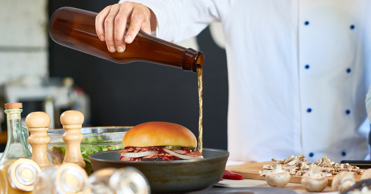 A photo of a chef pouring beer into a pan with a hamburger in it.